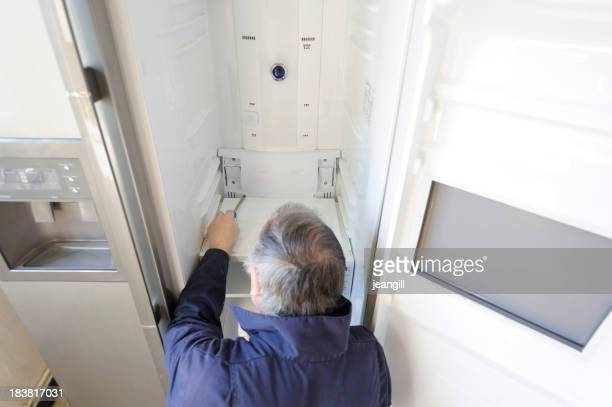 Man repairing refrigerator