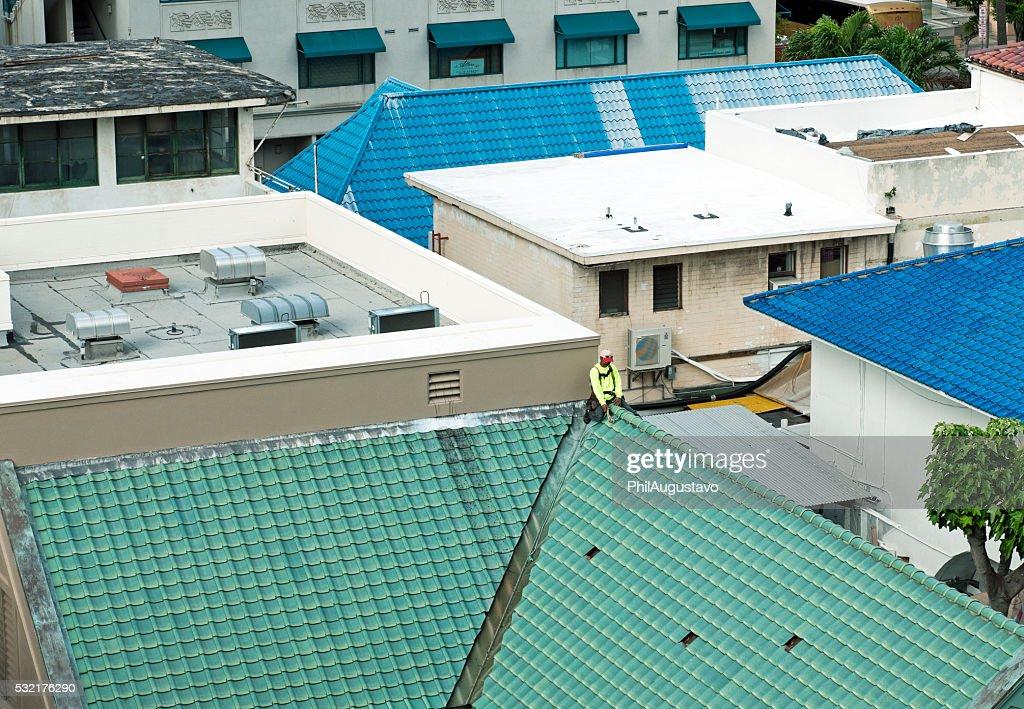 Man Repairing Rooftop Tiles In Honolulu Hi Stock Photo