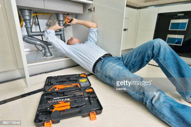 Man repairing sink pipe in the kitchen