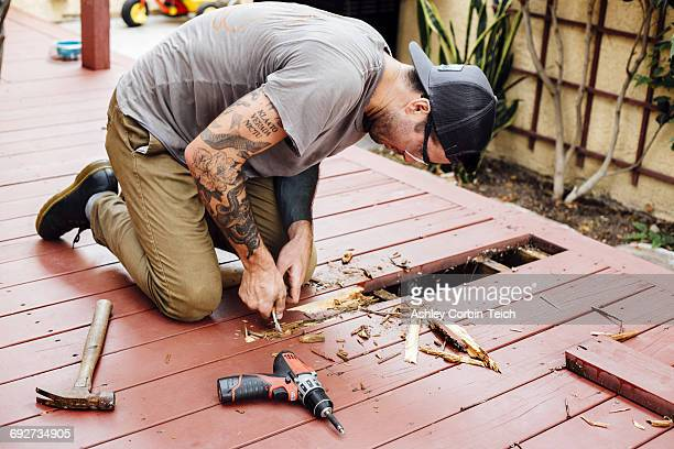 Man repairing wooden decking