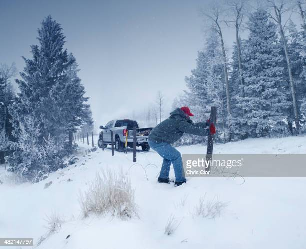 Man repairing wooden post in snowy ground