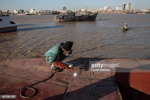 A man repairs a cargo ship on the banks of the Irrawaddy River on December 16 2013 in Yangon Myanmar Large cargo ships on the Irrawaddy River in...