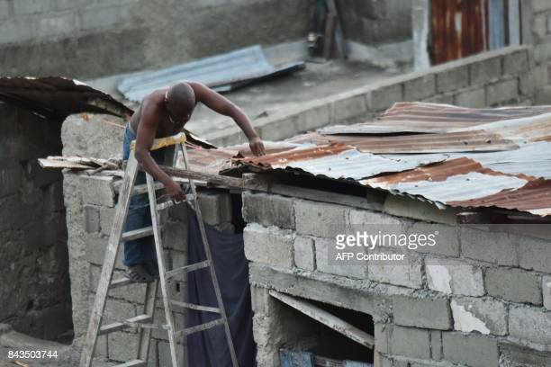 A man repairs a part of his roof in preparation for the arrival of Hurricane Irma in Lauriers neighborhood of CapHaitien on September 6 240 km from...