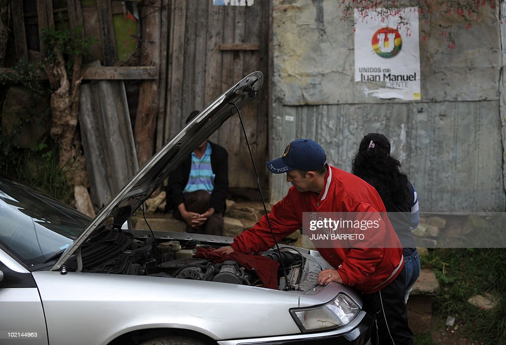 A man repairs his car next to a poster of Colombian presidential candidate Juan Manuel Santos, of the ruling National Unity party, in a populous neighborhood of Bogota on June 16, 2010. Juan Manuel Santos, the frontrunner to become Colombia's next president, said he would resume ties with neighbours Venezuela and Ecuador after months of bellicose relations. AFP PHOTO/Juan BARRETO