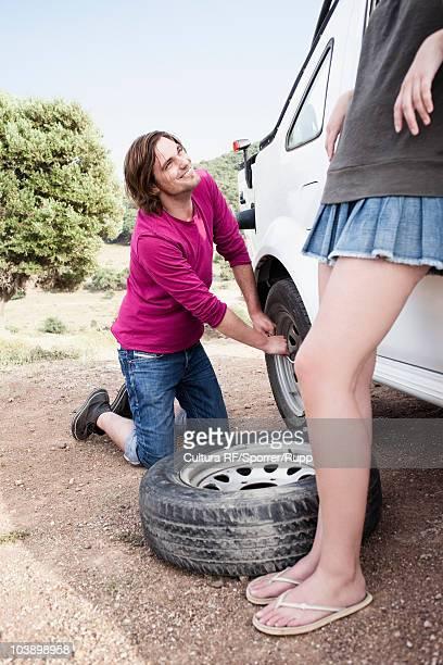 man replacing broken wheel - partire bildbanksfoton och bilder