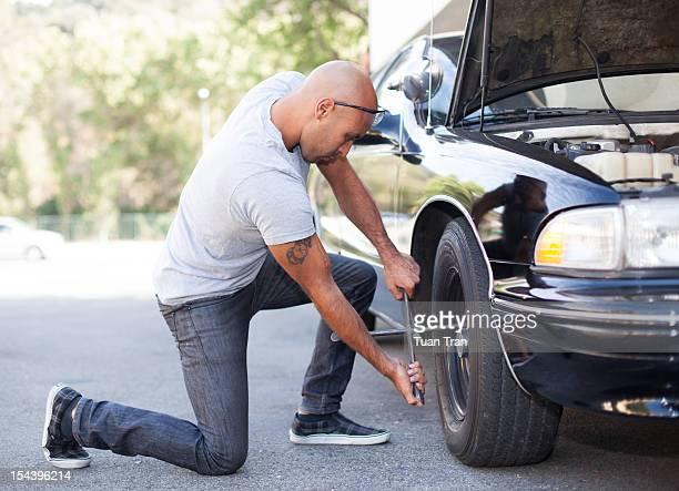 man replacing tire of car