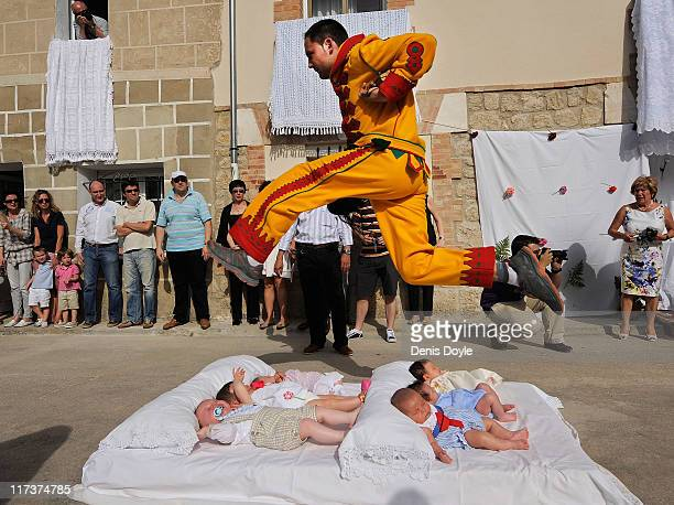 A man representing the devil leaps over babies during the festival of El Colacho on June 26 2011 in Castrillo de Murcia near Burgos Spain The...