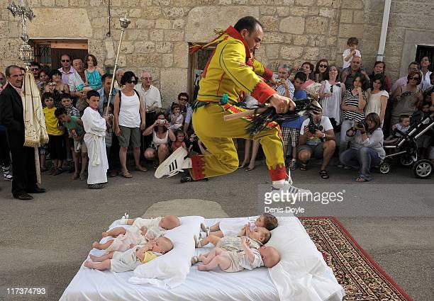 A man representing the devil leaps over babies during the festival of El Colacho on June 26 2011 in Castrillo de Murcia near Burgos Spain The...