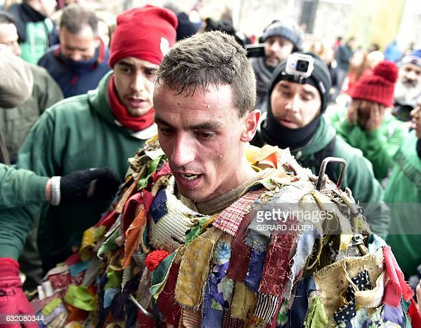 A man representing the Jarrampla without his mask sporting a costume covered in multicoloured ribbons and his face hidden behind a conical mask with...