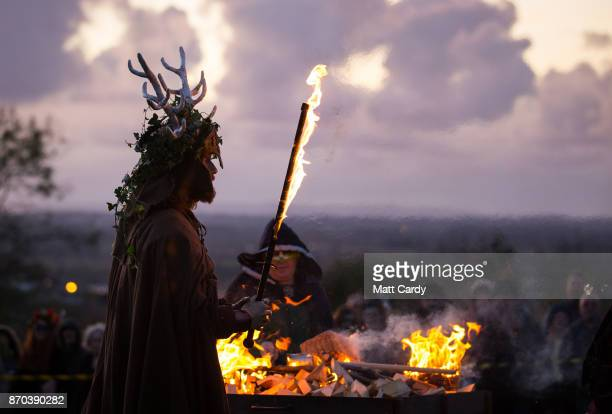 A man representing the Winter King holds a flaming sword as he takes part in a ceremony as they celebrate Samhain at the Glastonbury Dragons Samhain...