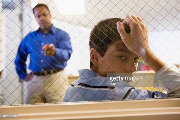 Man Reprimanding Boy Behind Fence