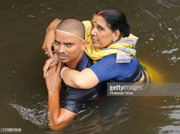 A man rescues his mother as they leave their residences in the waterlogged area of Rajender Nagar on October 1 2019 in Patna India At least 28 people...
