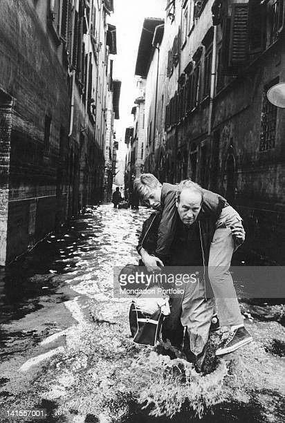 A man rescuing a boy on a flooded street of Florence Florence November 1966