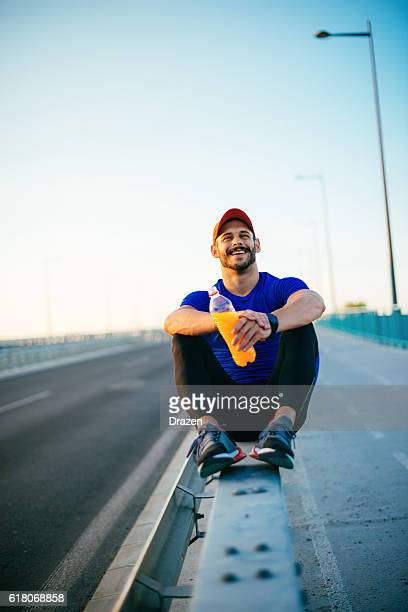 man resting after jogging and drinking energy drink - drazen stock pictures, royalty-free photos & images