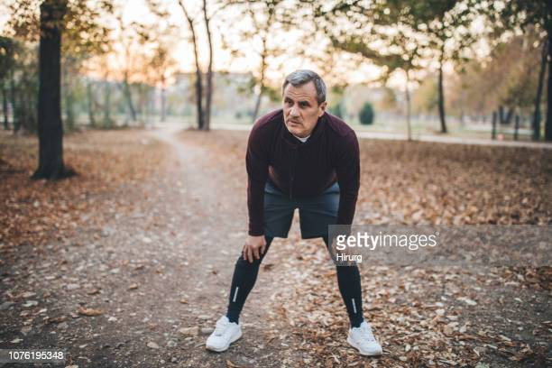 man resting after jogging - hand on knee stock pictures, royalty-free photos & images