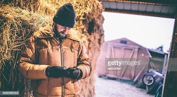 Man resting against hay in barn looks down at phone