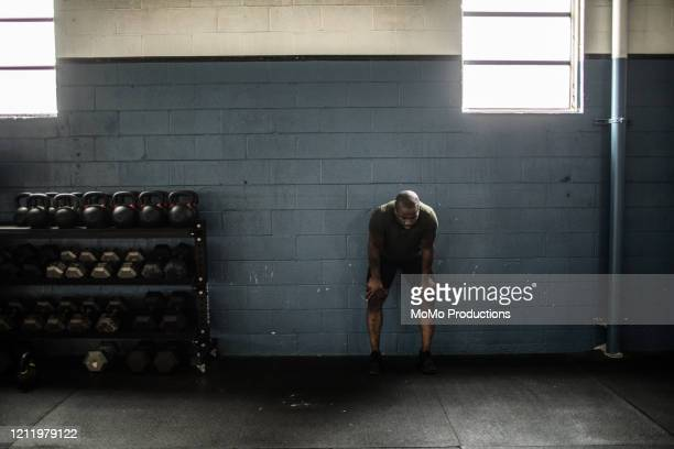 man resting against wall at cross training gym - muscular build stock pictures, royalty-free photos & images