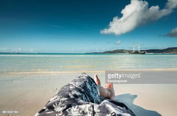 man resting alone in whitsunday beach in australia