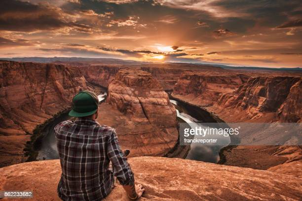 man resting at horseshoe bend in usa - north america stock pictures, royalty-free photos & images