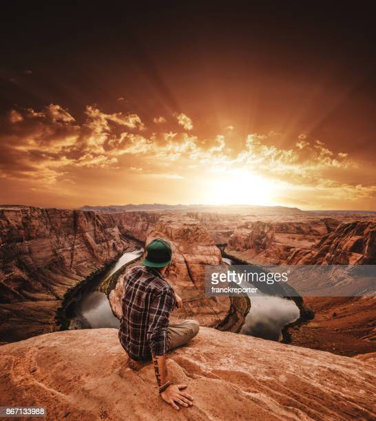 man resting at horseshoe bend in usa - category:grand_canyon_national_park stock pictures, royalty-free photos & images
