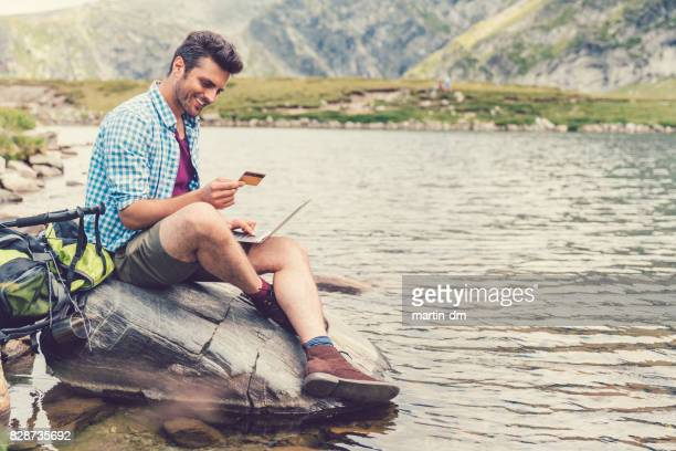 Man resting at the lake and shopping online with credit card