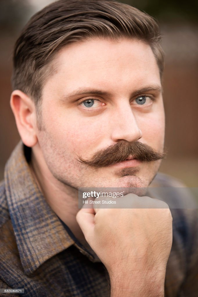 Man resting chin in hand outdoors : Stock-Foto