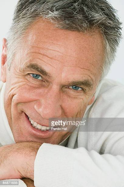 Man resting chin on arms, smiling, close-up