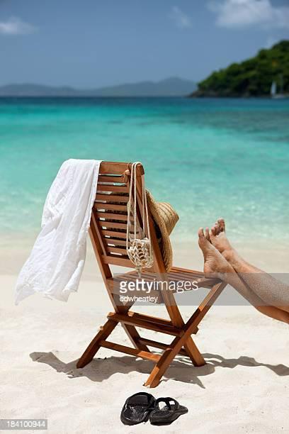 Homem descansar pés em uma cadeira na praia das Caraíbas