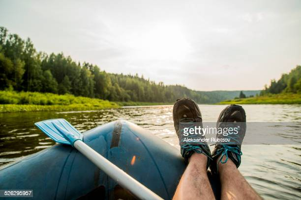 Man resting feet on boat in lake