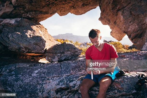 man resting from outdoor activity and eating energy bar - buitensport stockfoto's en -beelden