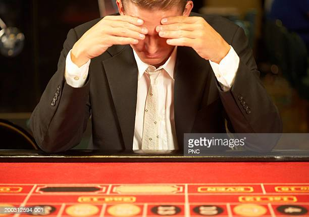 Man resting head in hands at game table in casino