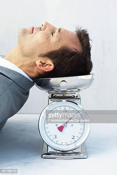 man resting head on scale, eyes closed - menselijk hoofd stockfoto's en -beelden