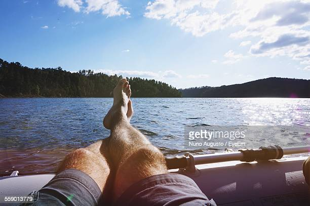 man resting his feet on side of pontoon - mujeres fotos stock pictures, royalty-free photos & images