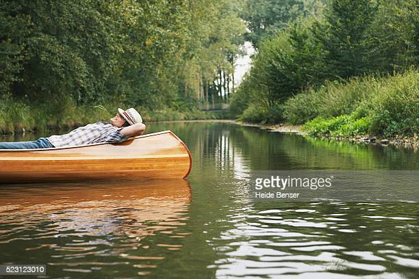 man resting in a canoe - flussufer stock-fotos und bilder
