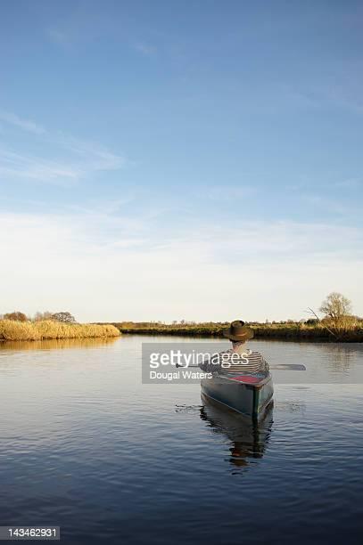 Man resting in canoe on river.