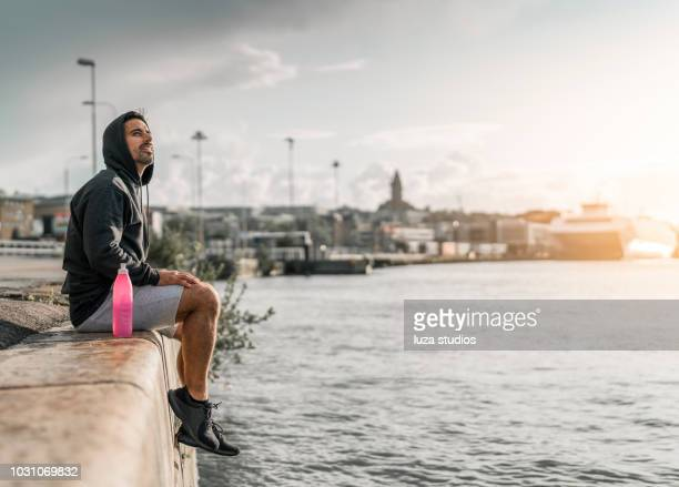 Man resting in the harbor after outdoor exercise