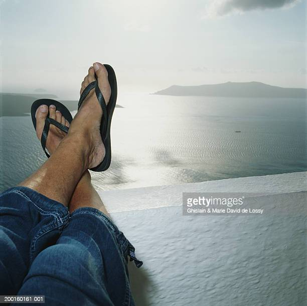 Man resting legs on wall overlooking ocean, low section