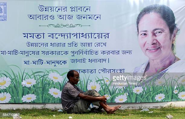 A man resting near huge banner of West Bengal Chief Minister Mamata Banerjee during her oath taking ceremony on May 27 2016 in Kolkata India The...