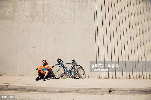 Man resting next to bicycle