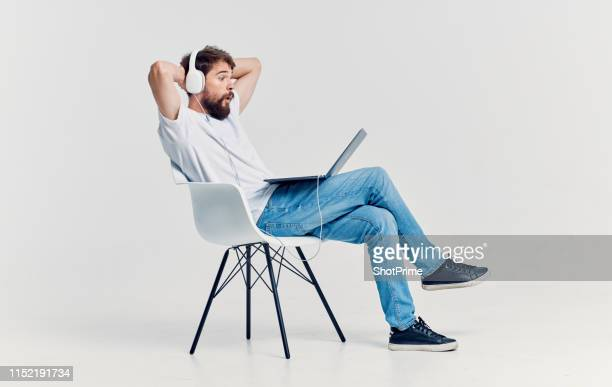man resting on a chair with a laptop and headphones - 椅子 ストックフォトと画像