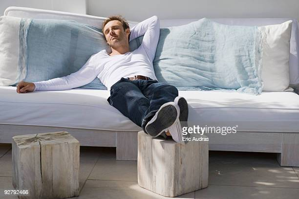 man resting on a couch - lying on back stock pictures, royalty-free photos & images