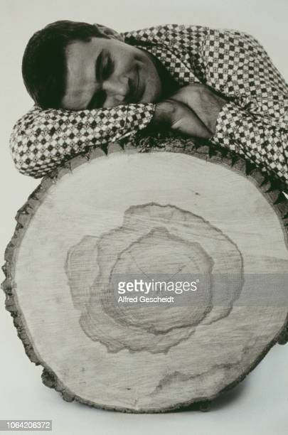 A man resting on a cut tree trunk US 1994