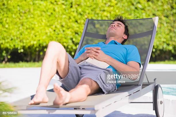 man resting on a lounge chair - chaise longue photos et images de collection