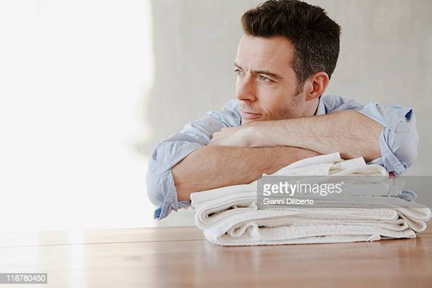 A man resting on a stack of folded laundry, day dreaming