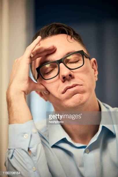 man resting on elbow with eyes closed - heshphoto imagens e fotografias de stock