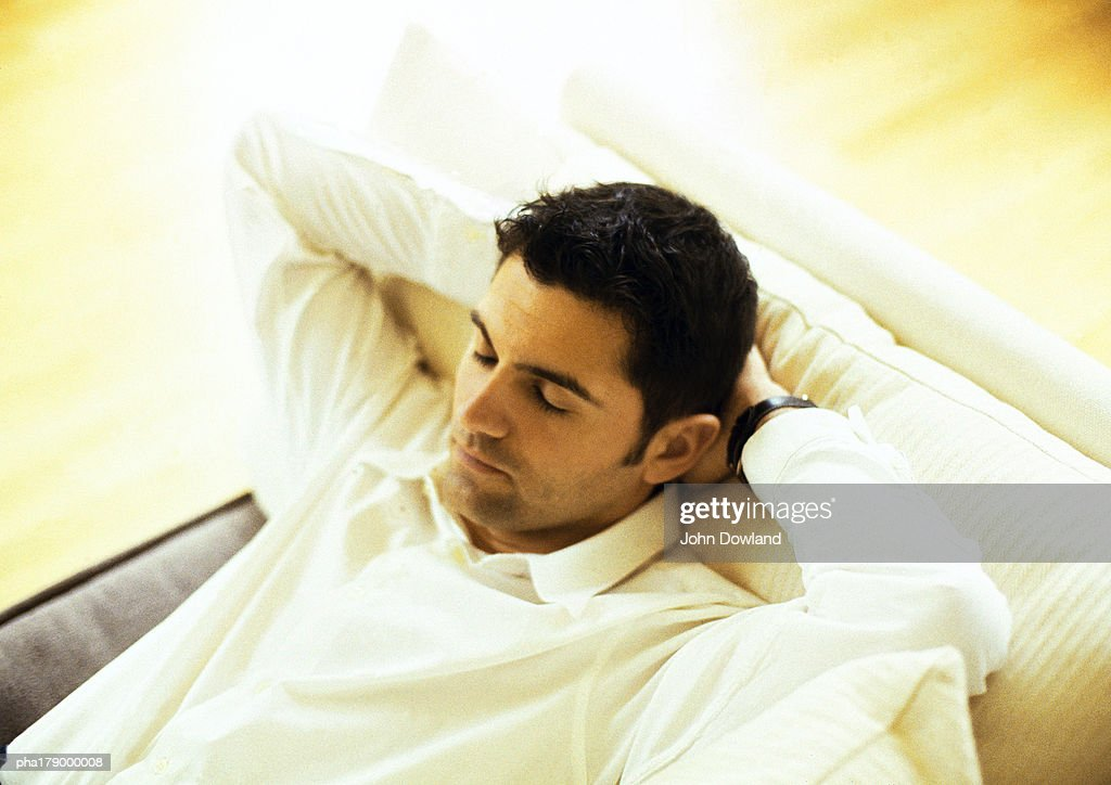 Man resting on sofa, close-up : Stockfoto
