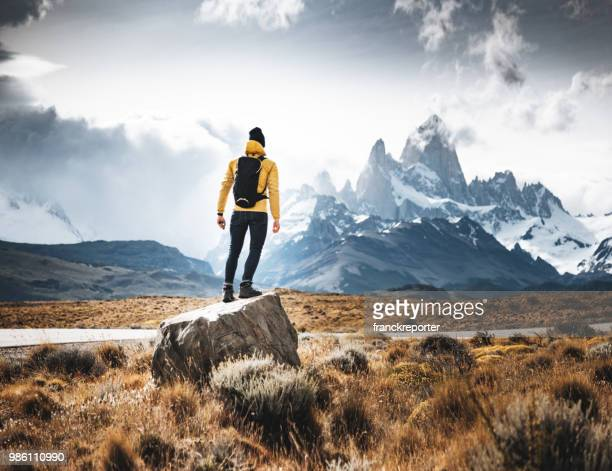 man resting on the rock in el chalten - impressionante foto e immagini stock