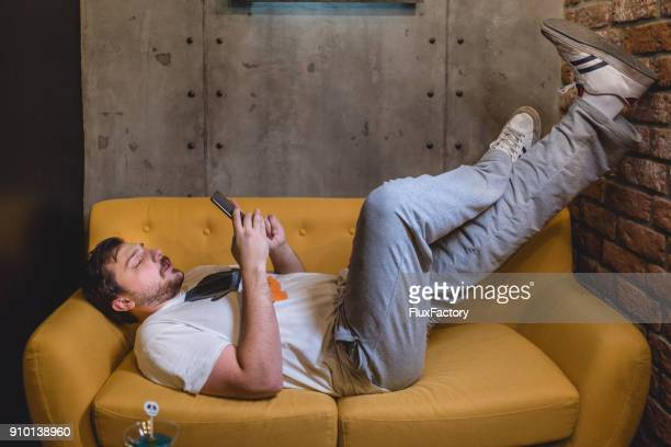 man resting on the sofa - laziness stock pictures, royalty-free photos & images