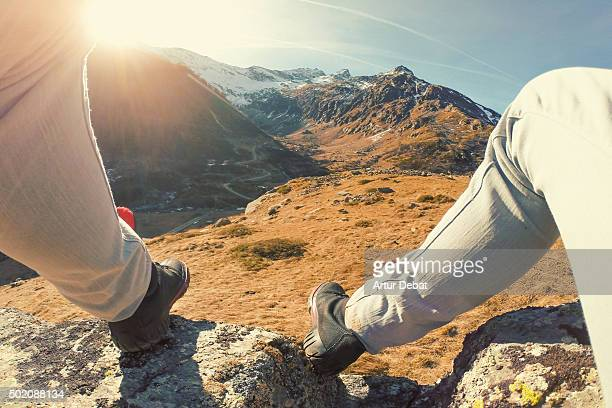 Man resting on top of rock in the Italian Alps with his legs from personal point of view.
