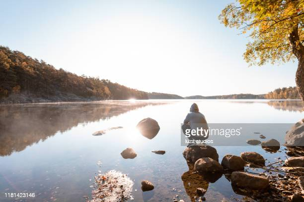 man resting out by the lake after an outdoor exercise - non urban scene stock pictures, royalty-free photos & images
